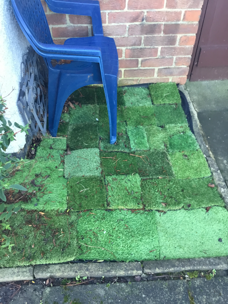 Samples of grass on outdoor patio with blue plastic chair