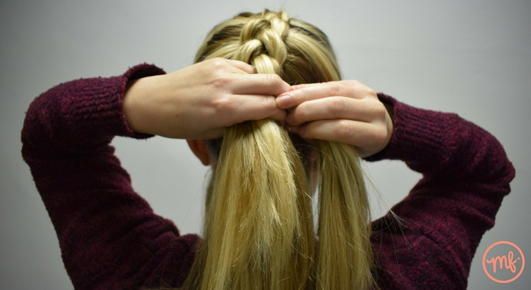 Blonde haired girl wearing a red jumper doing a dutch braid on herself