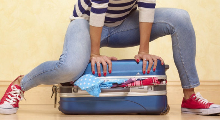 Woman struggling to pack a suitcase