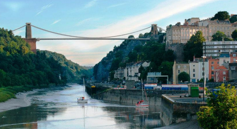 Sunset at Clifton Suspension Bridge, Bristol. Colourful houses to the side and two boats down the river