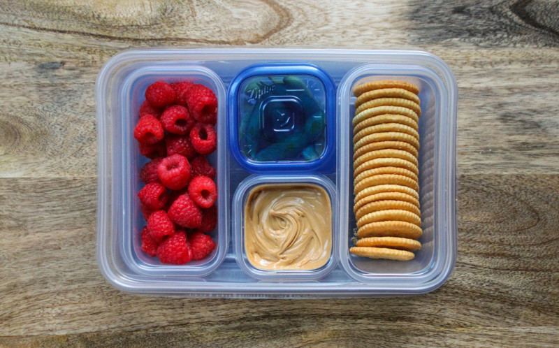 Ziplock tupperware filled with raspberries, peanut butter and biscuits