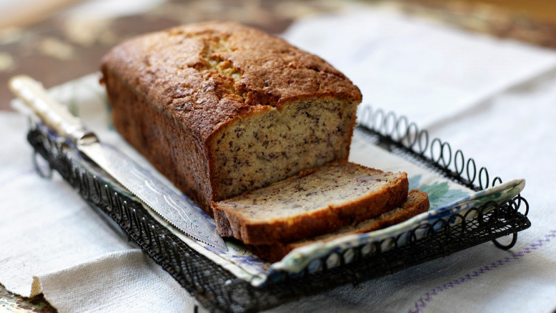 Cooked banana bread resting on a steel cake holder on top of a tea towel