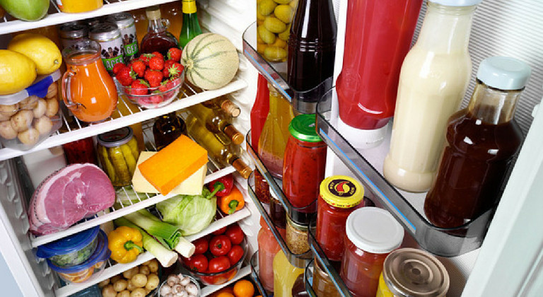 Open fridge filled with food, including veg, fruit, condiments, meats and juices
