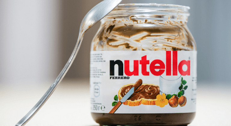 Spoon resting on empty jar of Nutella