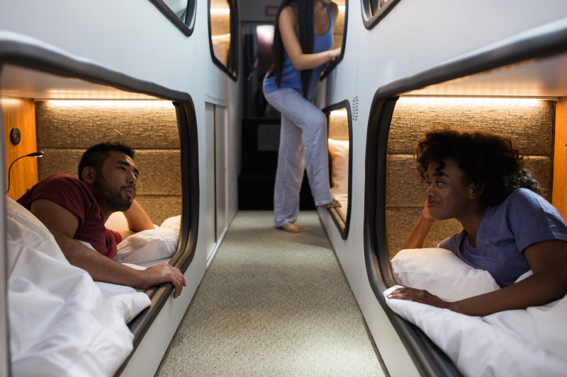 Man and woman talking while in sleeping pods on an overnight bus