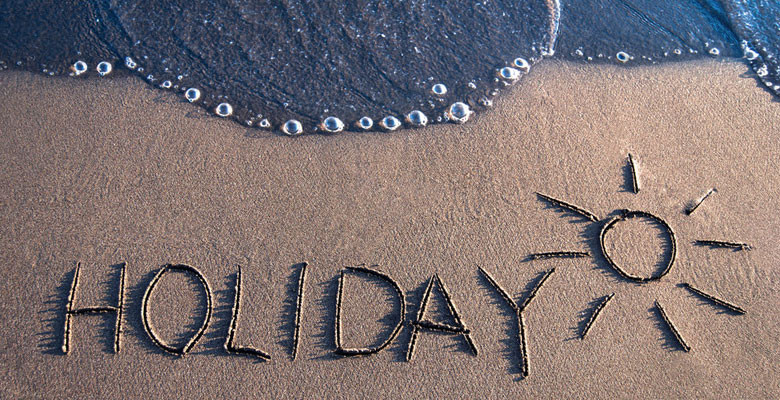 'Holiday' written on the sand with sea on the edge - photo taken from bird's eye perspective