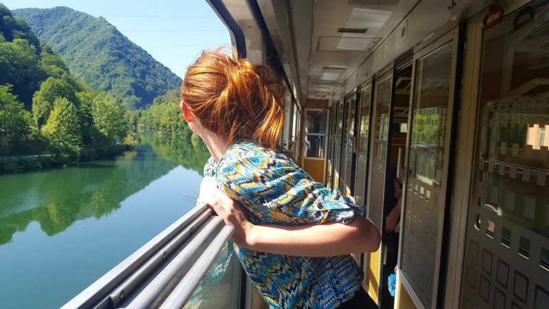 Red haired woman leaning over train rail to look at view of hills