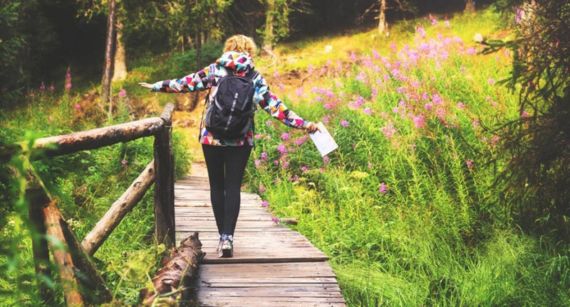 Back of woman walking across a wooden pathway, holding a map with a backpack on. Walking through a green woodland with flowers and trees all around