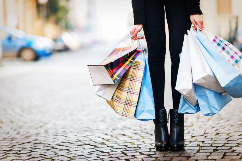 legs of a woman holding ten multicoloured shopping bags stood on a cobbled street