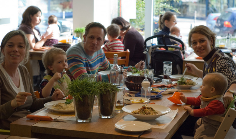 Family of five (including 3 children) out for dinner, sat at wooden table smiling at the camera