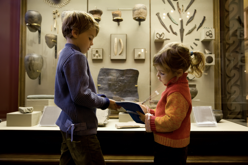 Young boy and girl in front of exhibition at a museum, writing in a blue notepad