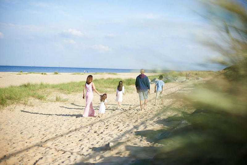 Family of five walking along a British beach