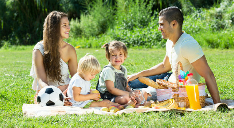 Parents with two daughters having picnic in a park
