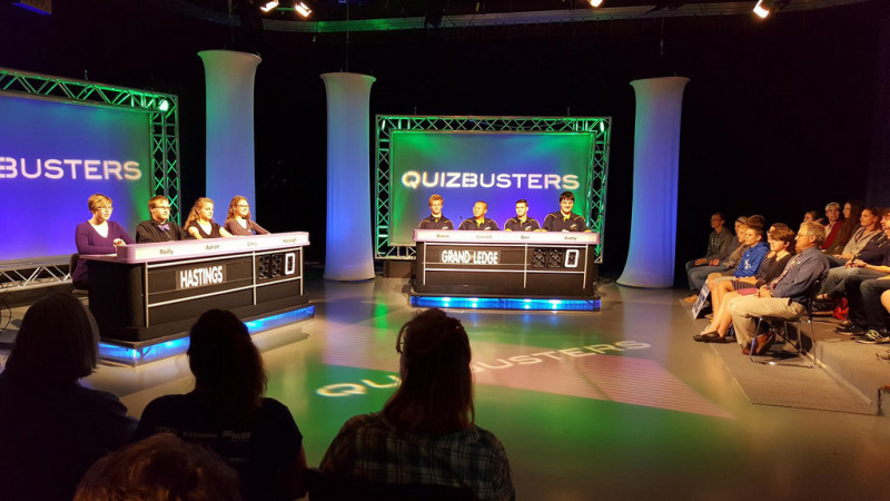 Behind the scenes of Quizbusters TV show recording. 2 panels facing audience members