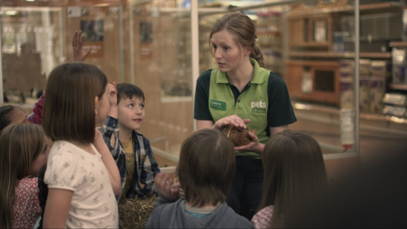 Pets At Home worker holding a guinea pig and talking to a group of children