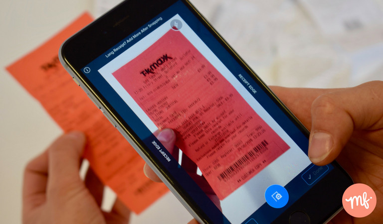 Hand holding black iPhone scanning a red TK Maxx receipt
