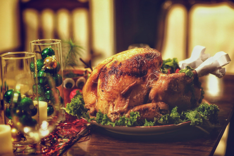 Cooked turkey on a decorated Christmas table, with 2 clear glasses filled with green baubles
