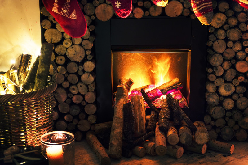 Fire place surrounded by wooden sticks and with stockings hanging on the fireplace