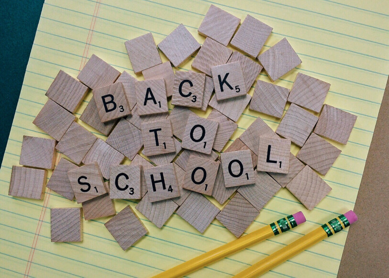 Back to school written on wooden scrabble blocks, placed on yellow lined paper