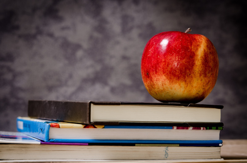 Red apple placed on top of stack of books