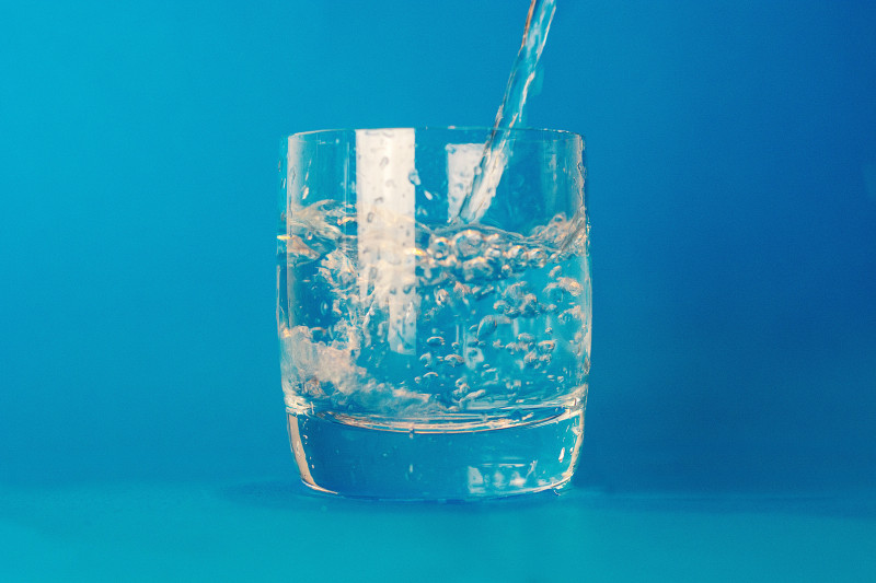 Water being poured into a glass tumbler on a blue background