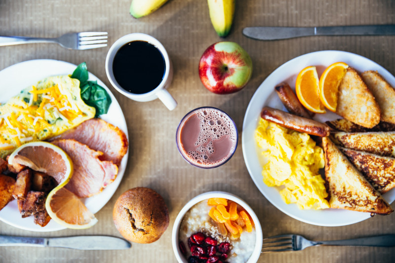 Birds eye view of 2 breakfast plates, with fried toast, sausages, scrambled eggs, bacon, coffee, fruit and granola.