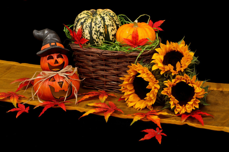 Halloween decorations of carved pumpkins, sunflowers, autumn leaves and a basket