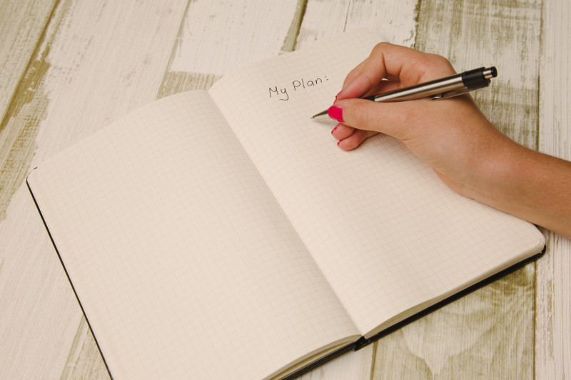 White female hand with pink nail varnish holding a black pen about to write in a notepad, on a page with the title 'My Plan'