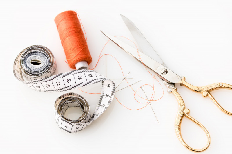 Birds eye view of tape measure, orange thread, pins and needles and a pair of scissors