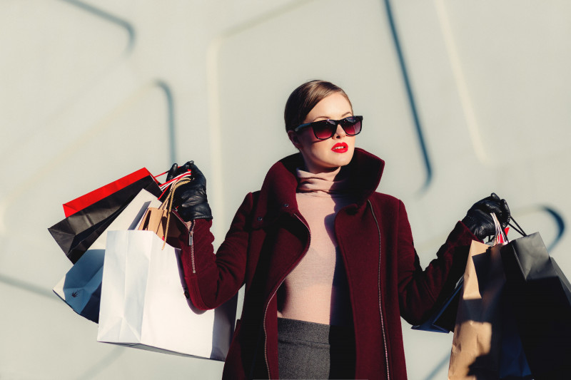 Glamorous woman wearing sunglasses, red lipstick and a red coat holding various shopping bags