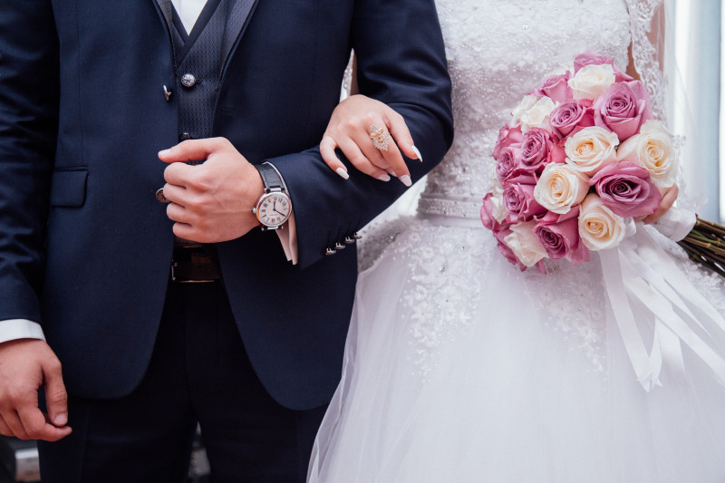 Bride and groom arm in arm on wedding day, holding pink and cream flowers