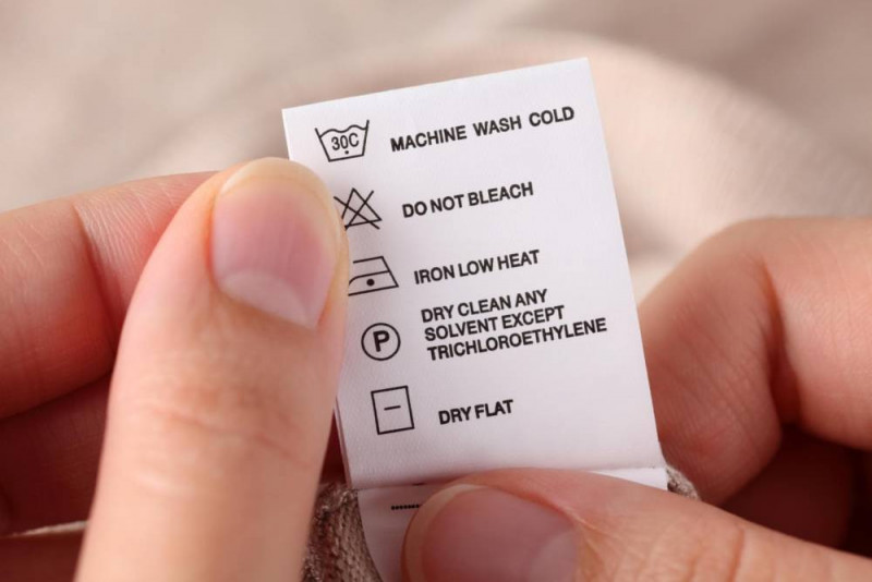 Hand holding a white clothes laundry label