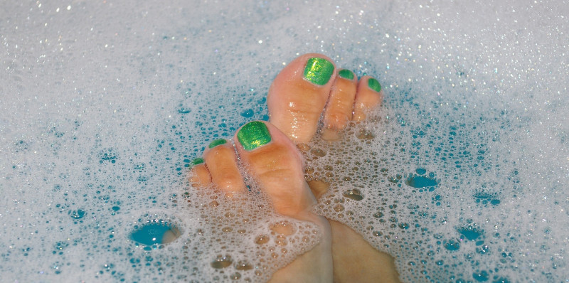 Feet with green toenails in a bubble bath