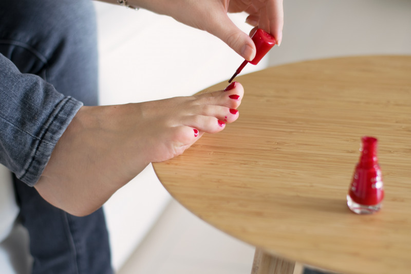 Person wearing jeans painting their toenails red, resting on a wooden table