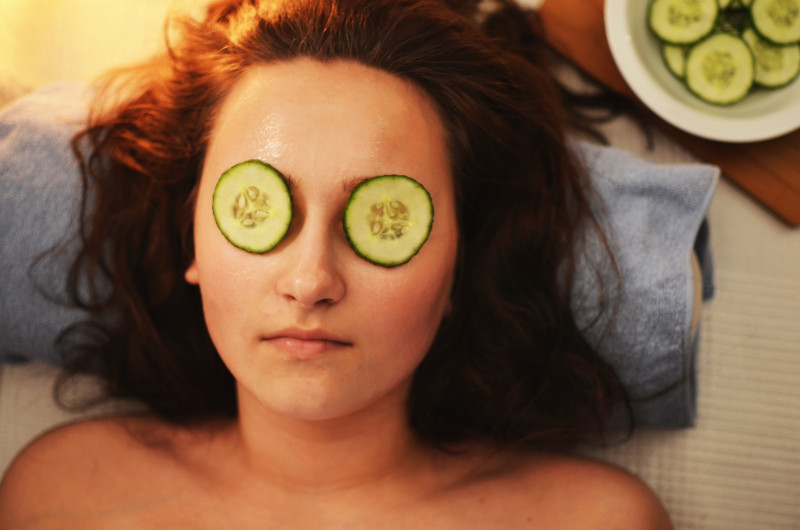 Brown haired woman relaxing with slices of cucumber on her eyes