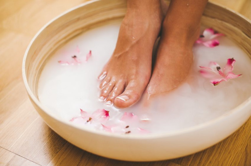 Pair of feet soaking in a bowl with flowers in