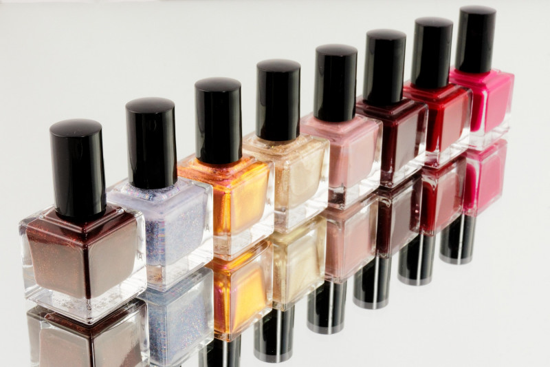 Eight nail varnishes in an array of colour line up on a mirrored background