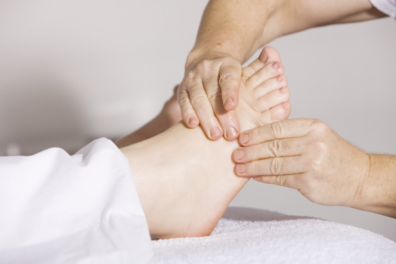 Close up of hand massaging foot wearing white trousers
