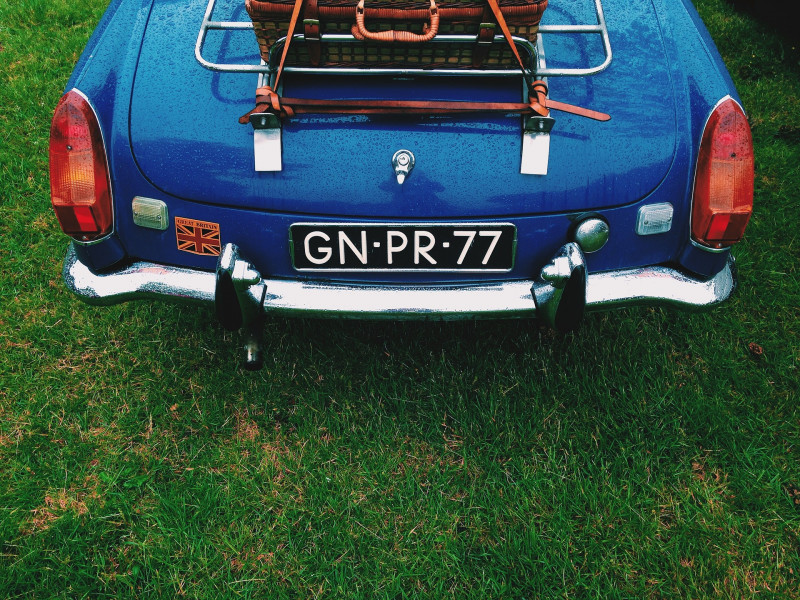 Boot of a blue car parked on green grass