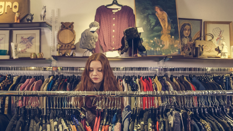 Red haired woman looking through rail of clothes in a charity shop