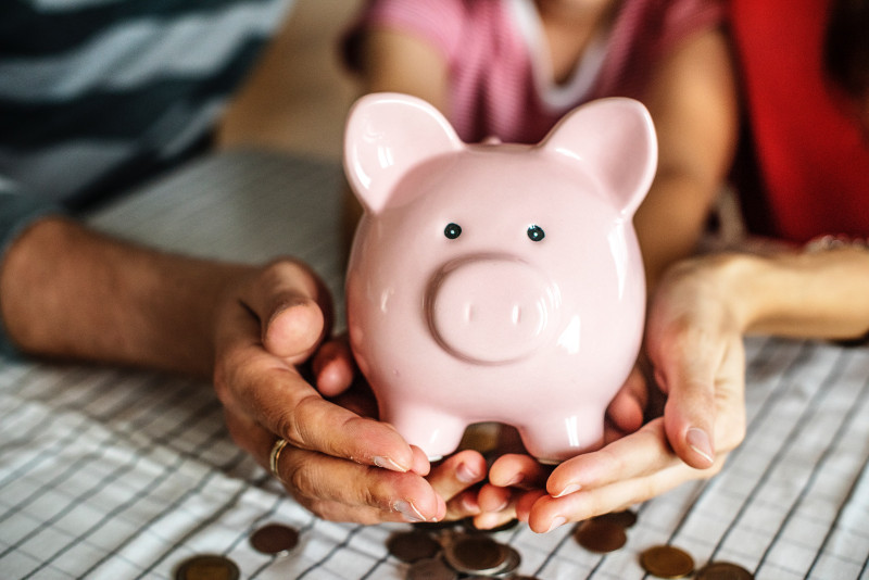 Two hands holding a pink Piggy Bank with coins out of focus below