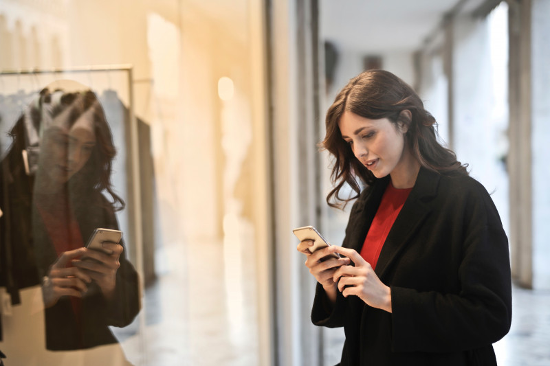 Brunette woman wearing red jumper and black coat looking at iPhone with reflection in mirror
