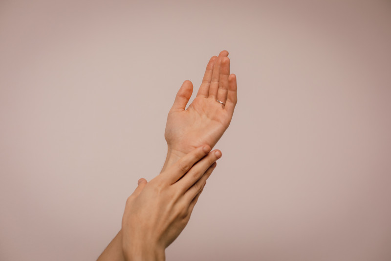 Pair of hands rubbing together against a pink background