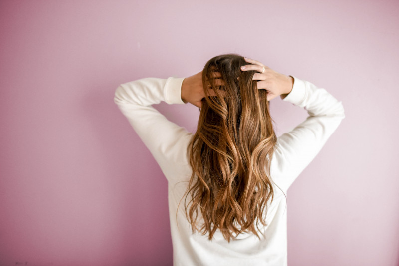 Image of the back of a dark blonde woman with hands running through hair, facing a pink background