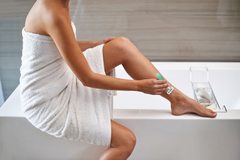 Woman shaving legs sat on the edge of white bath