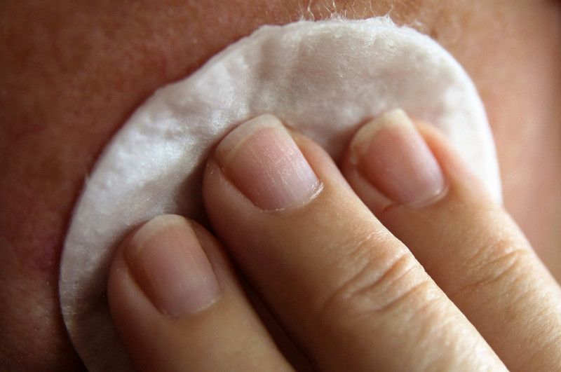 Close up of hand applying cotton wool to face