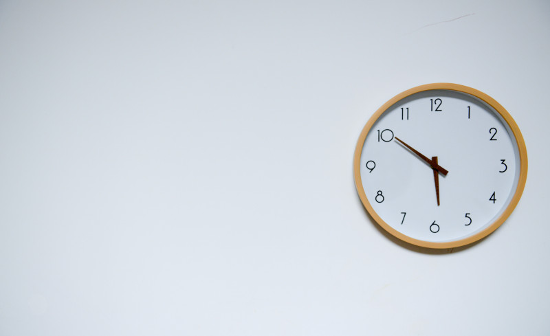 Clock face on a white wall at 5:50