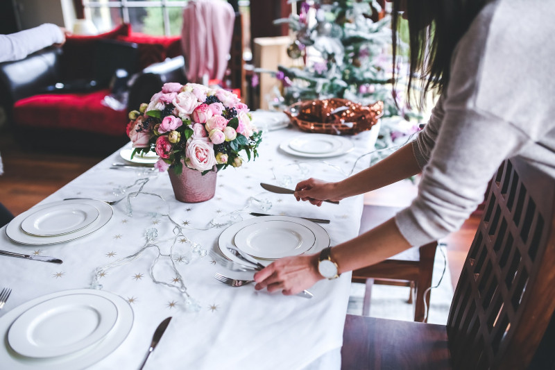 Woman setting up table for Christmas dinner