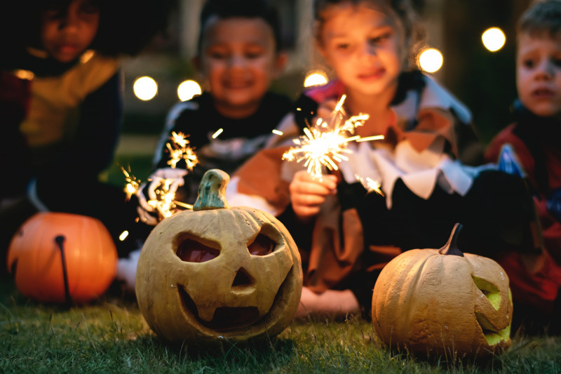 Carved pumpkins on the grass with children in the background playing with sparklers