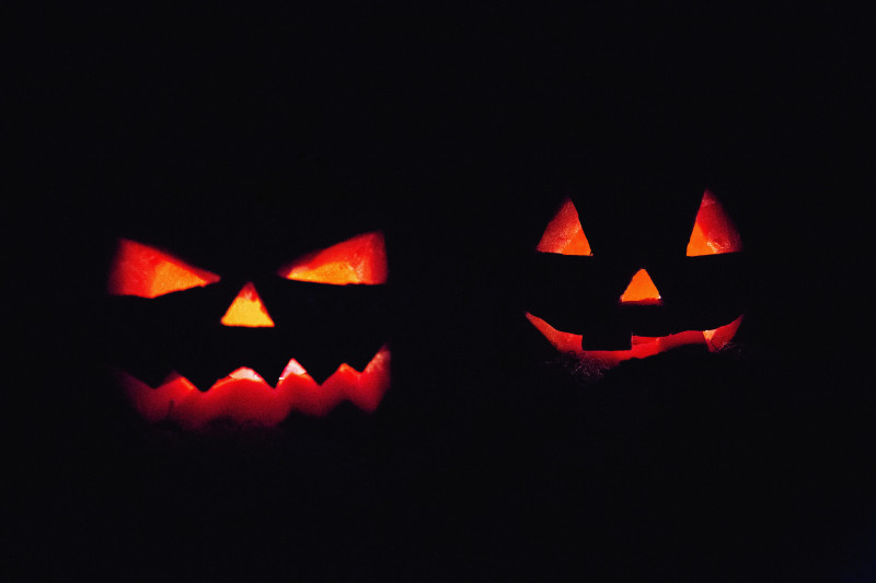 Silhouette of two lit up Halloween pumpkins